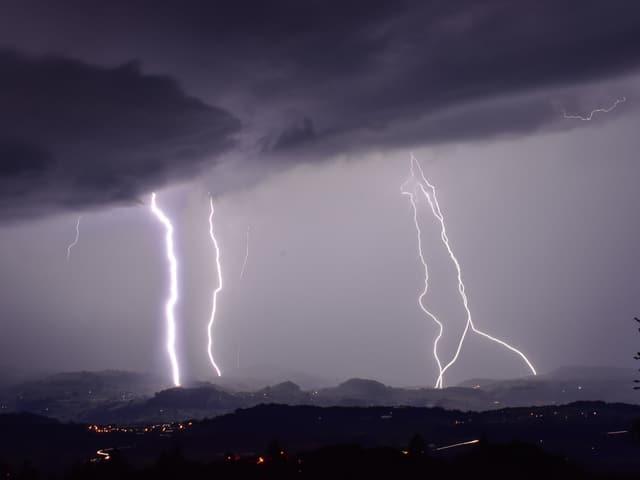 Violett dunkler Himmel mit 4 Blitzen, die auf den Boden einschlagen.