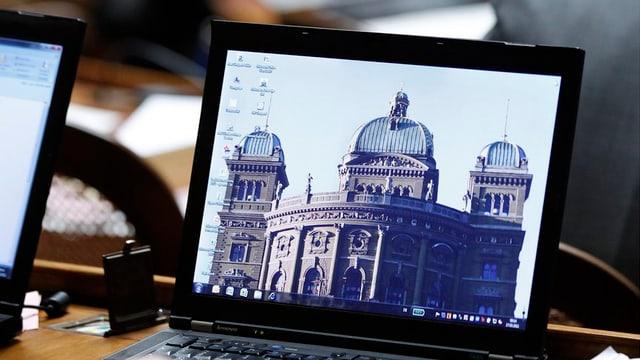 Ein Laptop auf dem Tisch eines Parlamentariers mit dem Bundeshaus als Desktop-Hintergrund.