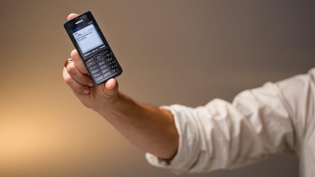 Ein kleines, schwarzes Handy – gehalten von nur zwei Fingern!
