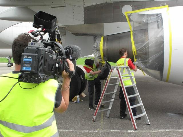 Zwei Männer enfernen Plastik von einem Triebwerk, im Vordergrund filmt ein Kameramann