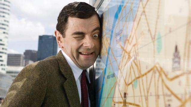 Auf dem Bild ist Mr. Bean zu sehen, wie er listig eine Karte von der Seite beäugt.