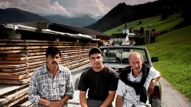Drei Männer sitzen vor einem Bretterstapel in der Landschaft.