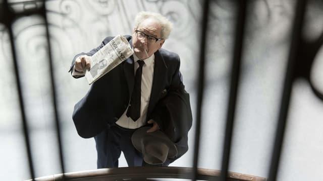 Schauspieler Burkhart Klaussner mit Zigarette im Mund und einer Zeitung in der Hand.