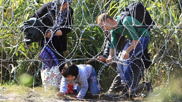Ein Mädchen kriecht unter einem Stacheldrahtzaun hindurch, ein Mann hilft ihr dabei, eine Frau steht daneben.