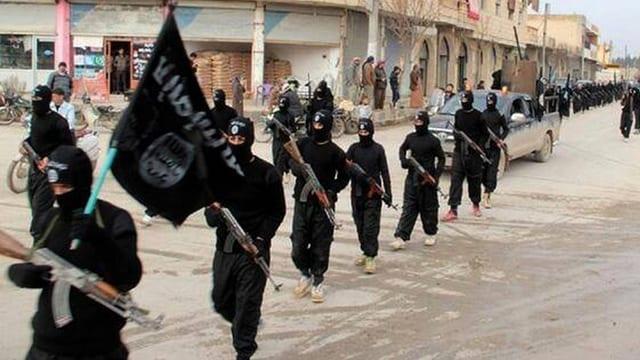 Schwarz gekleidete, vermummte und bewaffnete Dschihadisten defilieren auf einer Strasse.