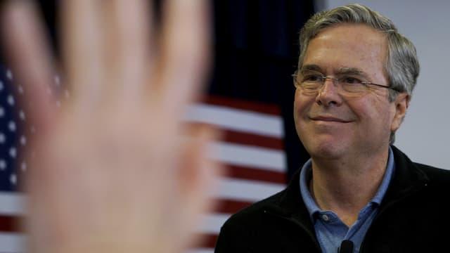 Jeb Bush vor US-Flagge. Verschwommen im Vordergrund: Aufgestreckte Hand eines Zuhörers.