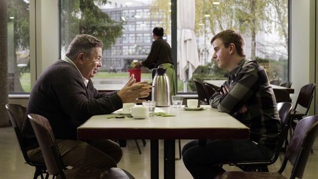 Zwei Männer diskutieren am Tisch.