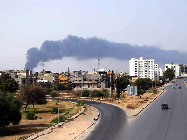 Eine Rauchsäule zieht über die Skyline von Tripolis, im Vorderdund eine fast leere Strasse, die abzweigt.
