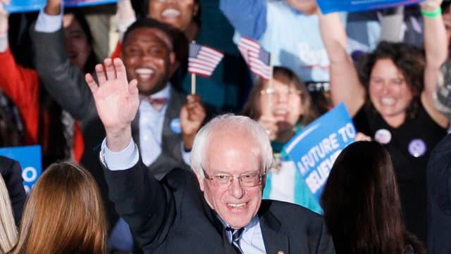 Sanders hebt, umringt von Anhängern mit Schildern und Fähnchen, seine rechts Hand.
