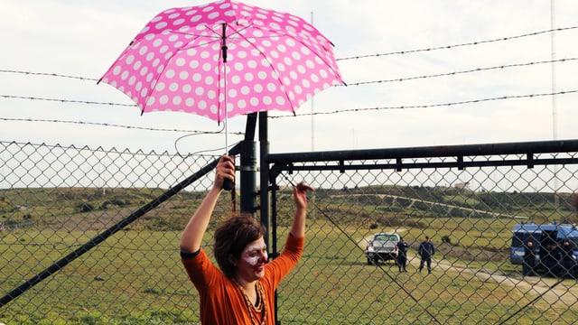 Frau mit geschminktem Gesicht steht mit einem bunten Regenschirm vor einem Maschendrahtzaun.