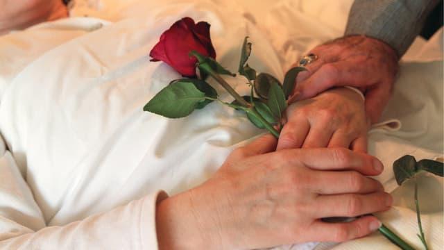 Eine Frau liegt mit eine Rose in der Hand im Bett
