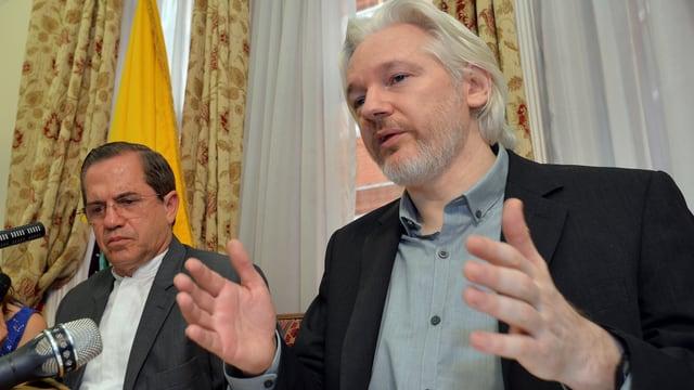 Assange (rechts) spricht in ein Mikrofon und gestikuliert, neben ihm sitzt ein Mann mit Brille, es ist der Aussenminister Ecuadors.
