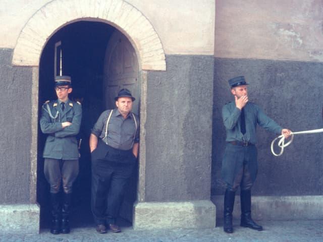 Ein Mann lehnt an einem Hauseingang. Links und rechts von ihm zwei uniformierte Männer.