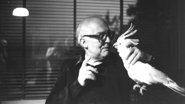 Schwarzweiss Foto eines Mannes mit dicker, schwarzer Brille, der einen Kakadu in der Hand hält und ihn anschaut.