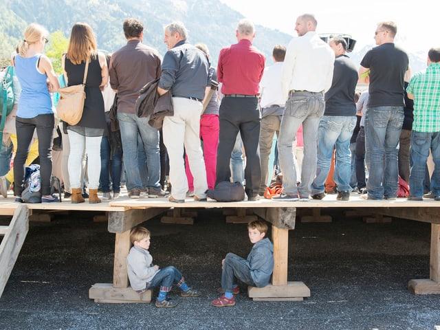 Zwei Jungen an der Landsgemeinde in Glarus sitzen unter einer Tribüne.