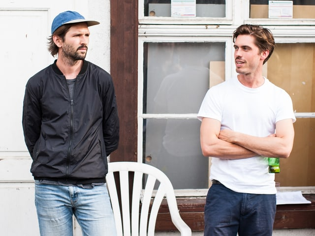 Zwei Männer stehen rum, einer hat eine Kappe, der andere eine kleine Bierflasche.
