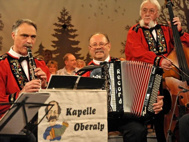 Drei Volksmusikanten in roten Sennenhemden mit Klarinette, Akkordeon und Kontrabass.