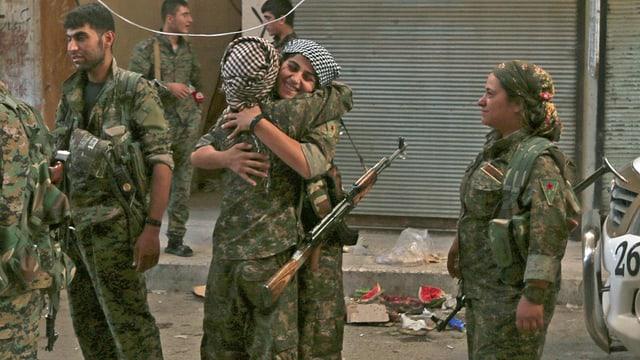 Kurdische Kämpferinnen umarmen sich.