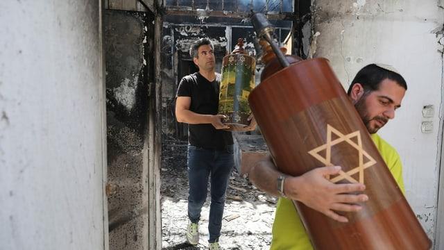 Zwei Männer tragen Thora aus einer Brandruine.