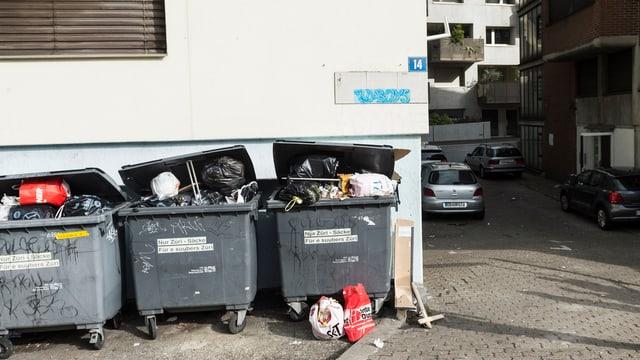 Eine Hausfassade, davor drei Container, randvoll mit Abfallsäcken und sonstigem Müll.