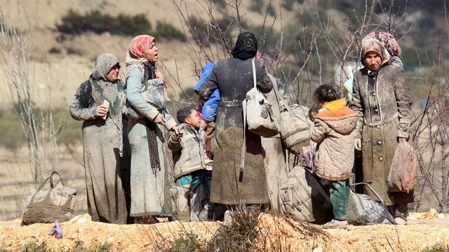Frauen und Kinder stehen zwischen Sträuchern herum, sie sind von der Flucht sichtlich mitgenommen.
