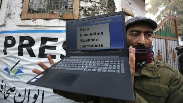 Mann mit Laptop auf dem steht: «stop humiliating kashmiri journalists»
