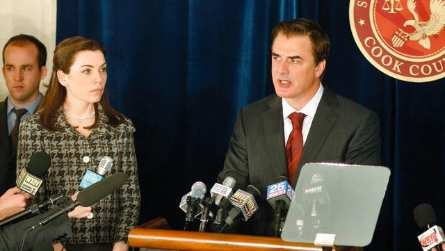 Ein mann gibt eine Pressekonferenz. Neben ihm steht seine Frau mit einem entgeisterten Gesichtsausdruck.