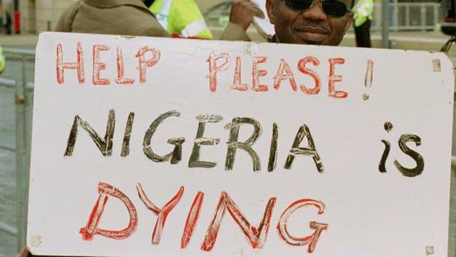 Ein Mann hält ein Transparent mit der Aufschrift «Help please, Nigeria ist dying»