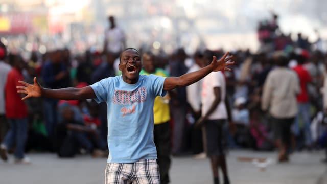 Junger Mann im Vordergrund mit ausgebreiteten Armen, er ruft etwas, dahinter eine Menschenmenge.