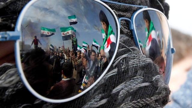 In den Gläsern einer Sonnenbrille spiegeln sich demonstrierenden Syrern in Jordanien.