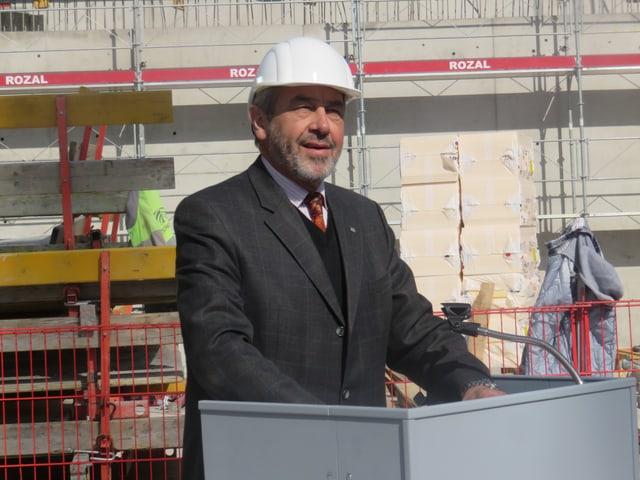 François Genoud am Rednerpult mit Bauhelm.