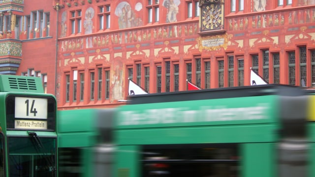 Mehrere Trams stehen und fahren vor dem Rathaus.