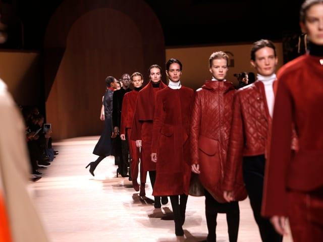 Mehrere Models auf Laufsteg in Weinrot