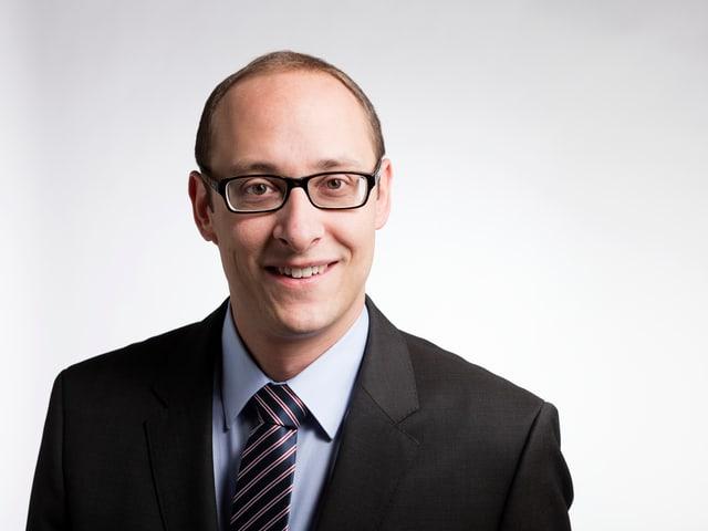 Martin Candinas mit gestreifter Krawatte und Brille.