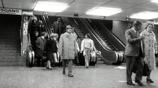 Menschen auf einer Rolltreppe.
