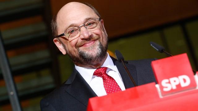 Martin Schulz lächelt an einem SPD-Pult stehend.