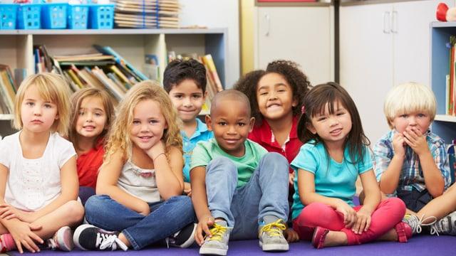 Schulkinder, die auf dem Boden sitzen.