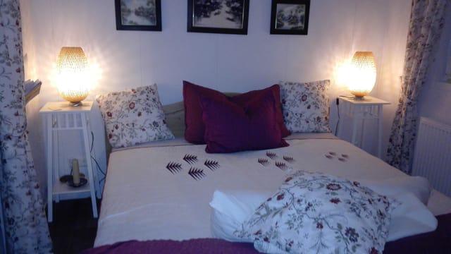 Bett mit weisser Decke und dunkelroten Kissen.