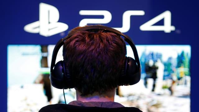 Ein Junge mit Kopfhörern spielt ein Playstation-4-Game.