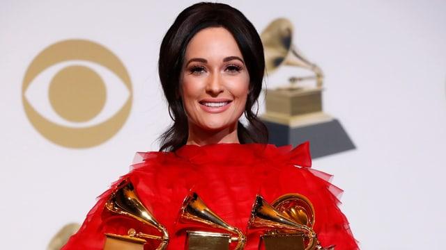 Kacey Musgraves hält drei Grammys in der Hand.