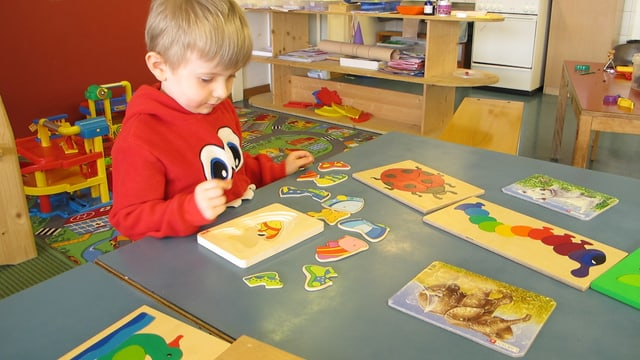 Kind löst Puzzle im Kindergarten