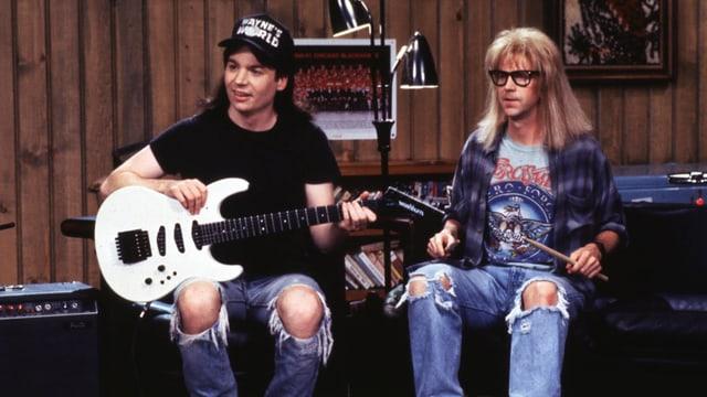 Wayne und Garth mit Gitarre und Schlagzeugstöcken.