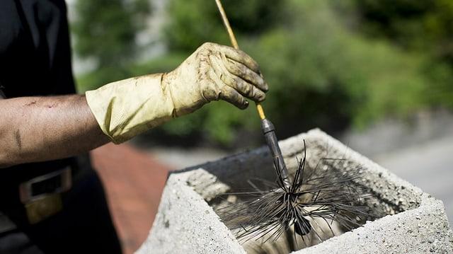 Eine Hand reinigt einen Kamin.