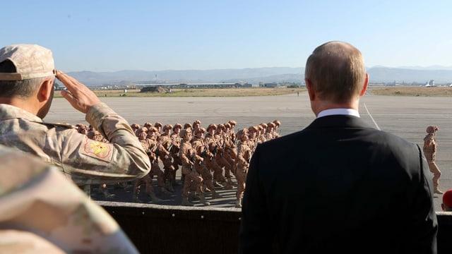 Putin nimmt auf einem flugfeld ein Defilee von Soldaten ab.