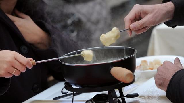 Menschen essen zusammen Käsefondue.