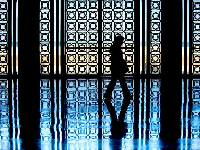 Eine Frau läuft durch eine Moschee, man sieht nur ihre Silhouette.
