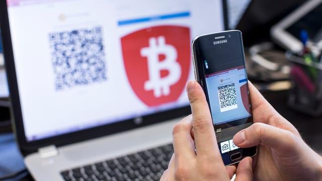 Ein Smartphone in zwei Händen gehalten, darauf ein Code. Im Hintergrund ein Laptop mit dem Bitcoin-Symbol.