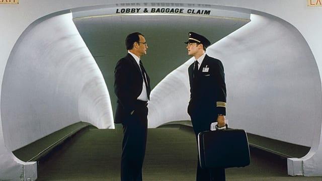 Zwei Männer in Anzügen stehen sich vor einem langen Gang gegenüber.