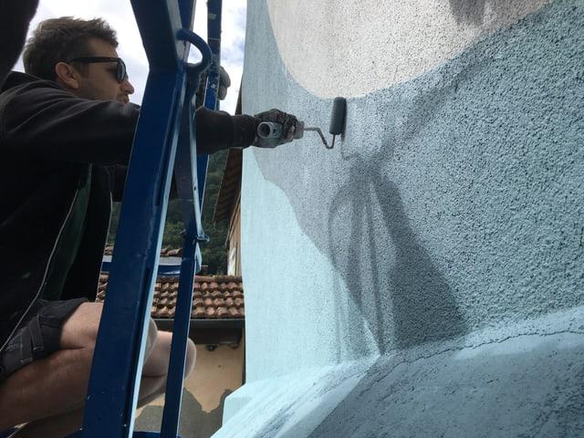 Künstler bringt mit Roller Farbe auf die Fassade.