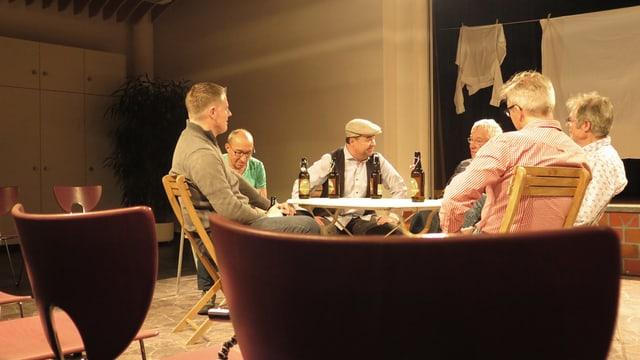 Männer sitzen um einen Tisch und diskutieren bei Bier.